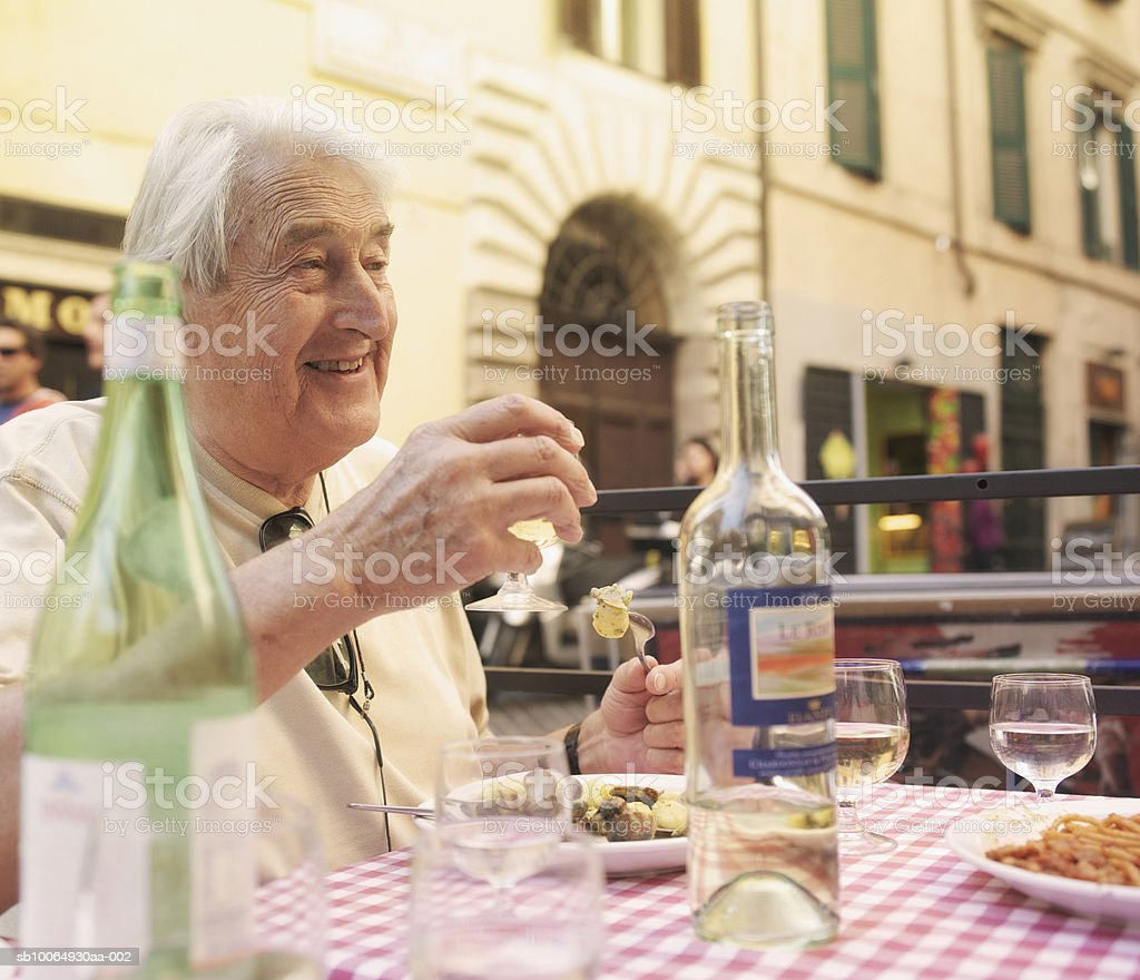 Senior man drinking wine at restaurant, smiling photo libre de droits
