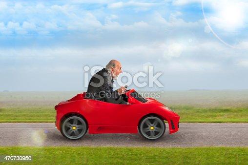 1035136022 istock photo senior man driving a toy racing car 470730950