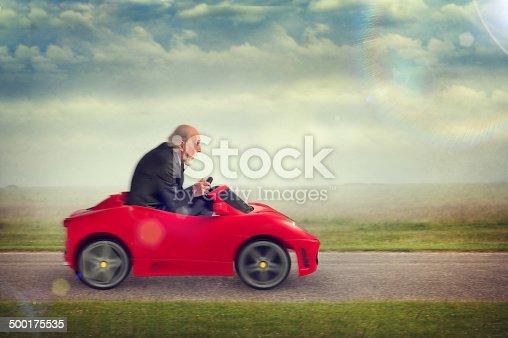 1035136022 istock photo senior man driving a toy racing car 500175535