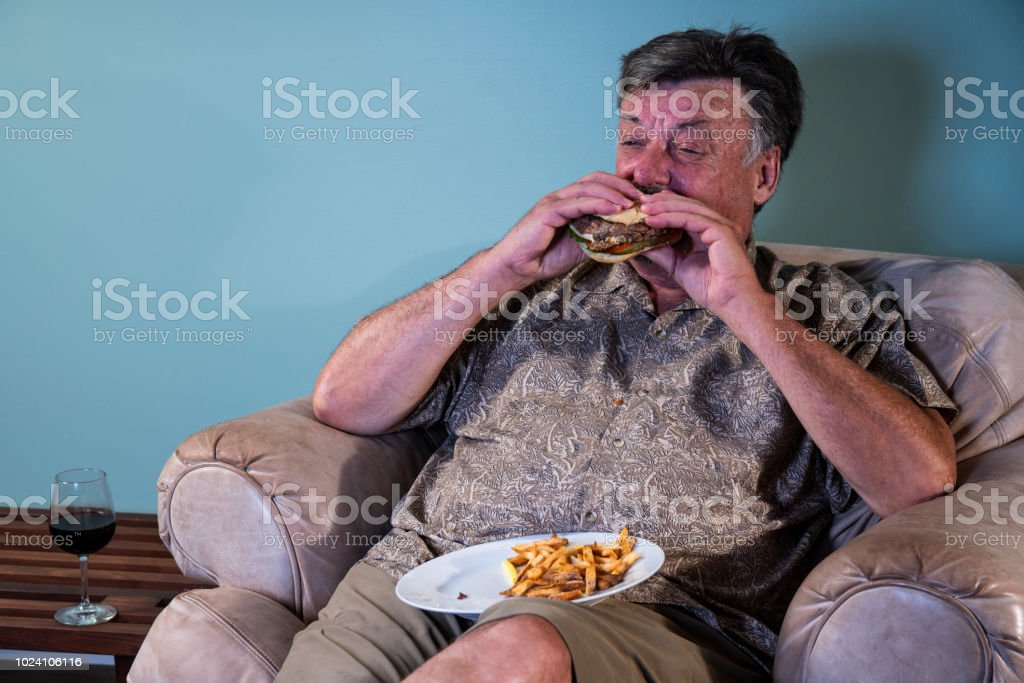 A senior man eating a large unhealthy meal of hamburger and french fries at home in an old easy chair stock photo