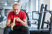 Senior man eating banana sitting at gym. Mature man eating banana during rehabilitation in gym.