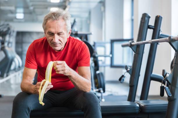 Ältere Menschen essen Bananen während der Rehabilitation im Fitness-Studio – Foto