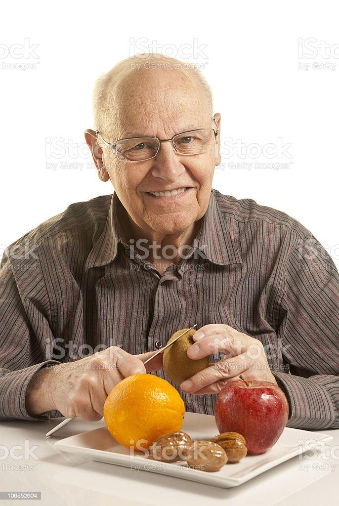 Senior man eating fresh fruit royalty-free stock photo