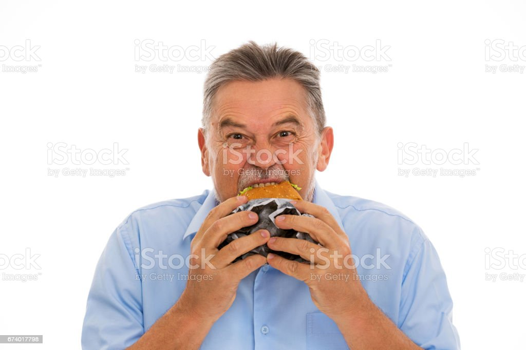 Senior man eating hamburger royalty-free stock photo