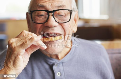 A senior man enjoys a bite of his toasted bread spread with sweet jelly jam preserves during breakfast at a restaurant. Selective focus on the toast and jelly.