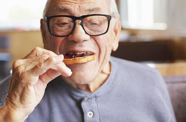 senior man eating toast and jelly jam - 咬 個照片及圖片檔