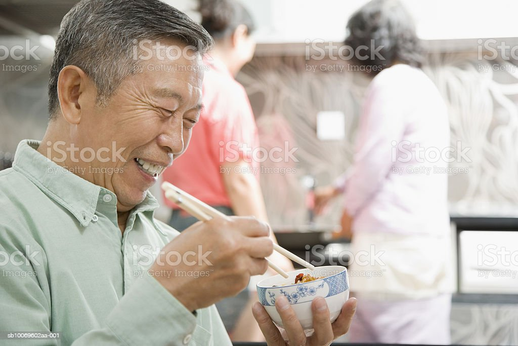 Senior man eating with chopsticks, women in background foto royalty-free