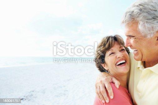 istock Senior man embracing a smiling woman on beach 183061757