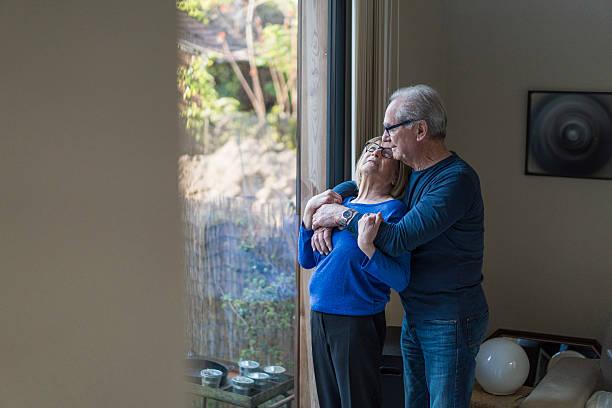 Senior man embracing woman at home stock photo