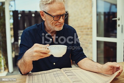 116379055 istock photo Senior man enjoying his coffee and reading a newspaper outside 969571714