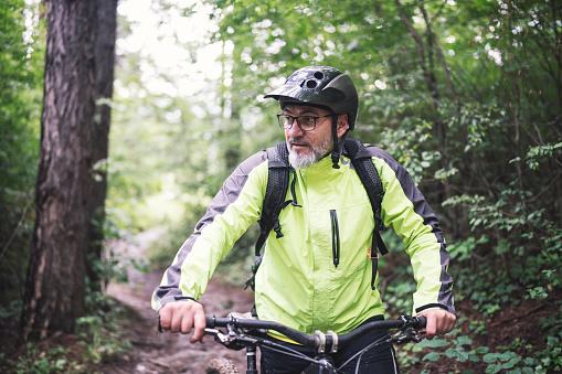 Senior biker pushing his mountain bike in the forest, he looking away.