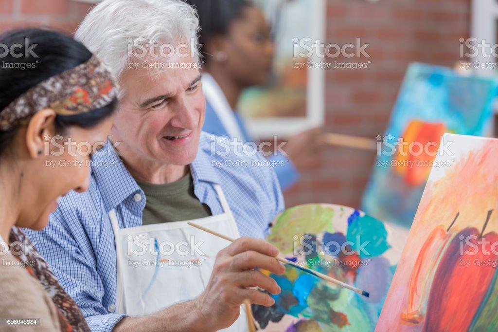 Senior man enjoys art class stock photo