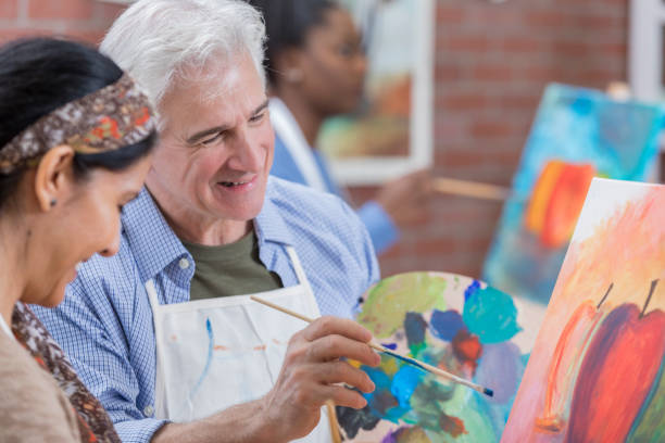 Senior man enjoys art class Confident retired senior Caucasian man paints with a female friend. alternative therapy stock pictures, royalty-free photos & images