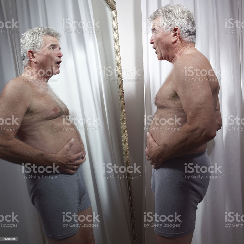 Senior man examines stomach in mirror royalty-free stock photo