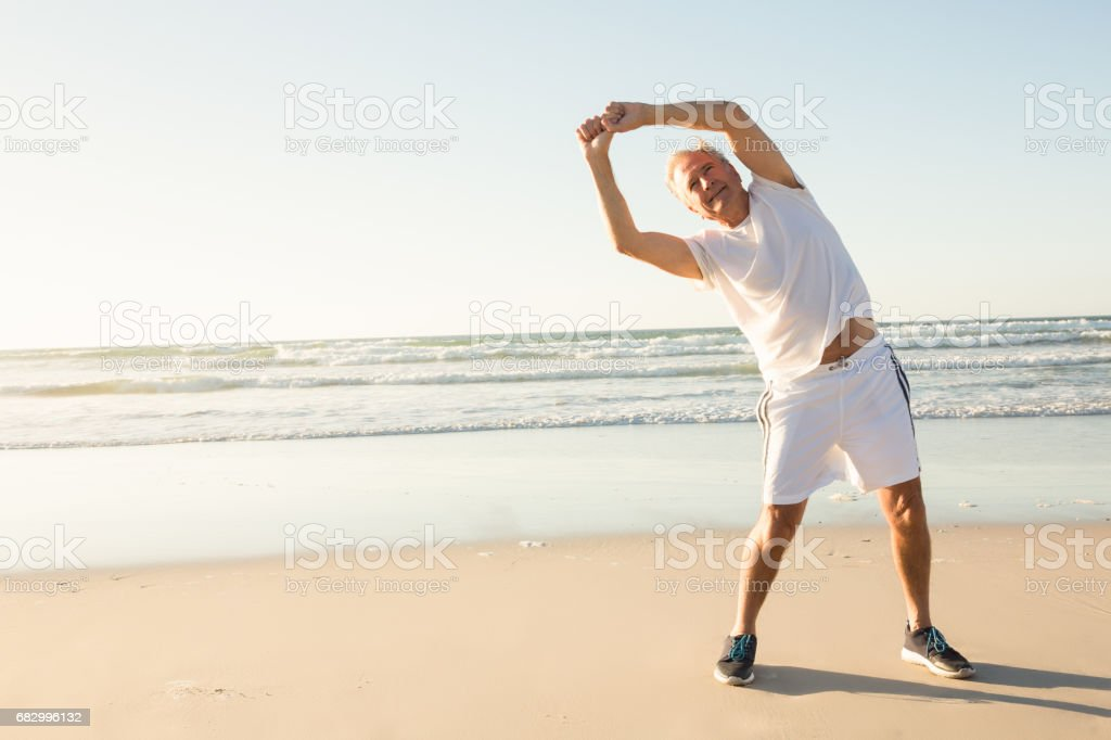 Senior man excersing while standing on sand foto de stock royalty-free