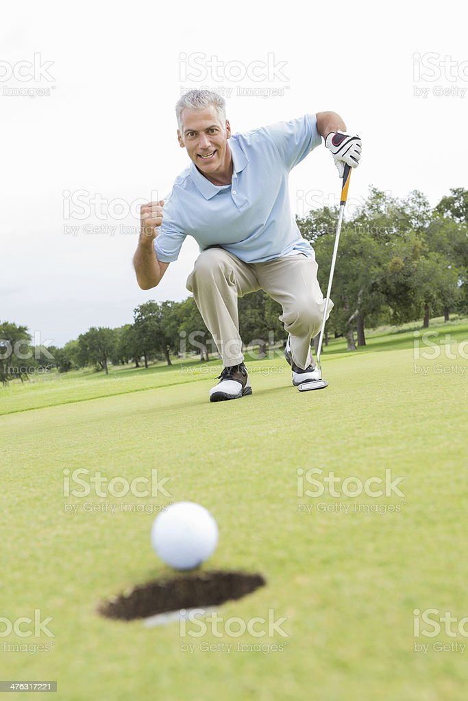 Senior man excited after putt during golf game stock photo