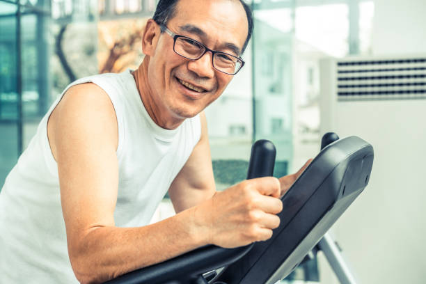 senior man exercise on treadmill in fitness center. mature healthy lifestyle. - runner rehab gym foto e immagini stock