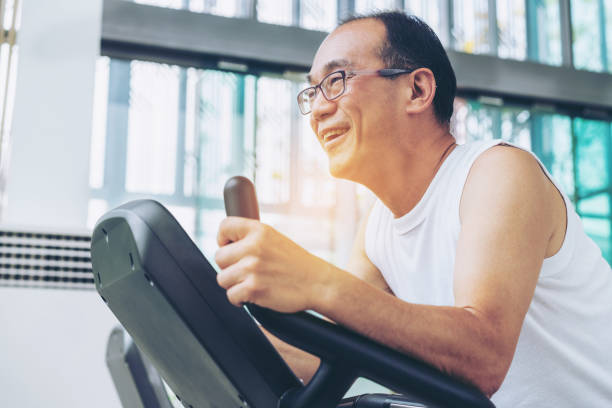 senior man exercise on treadmill in fitness center - runner rehab gym foto e immagini stock