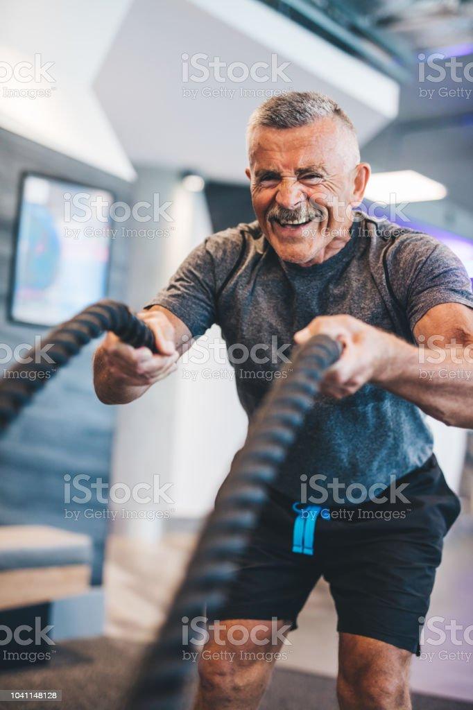 Senior hombre ejercicio con cuerdas en el gimnasio. foto de stock libre de derechos