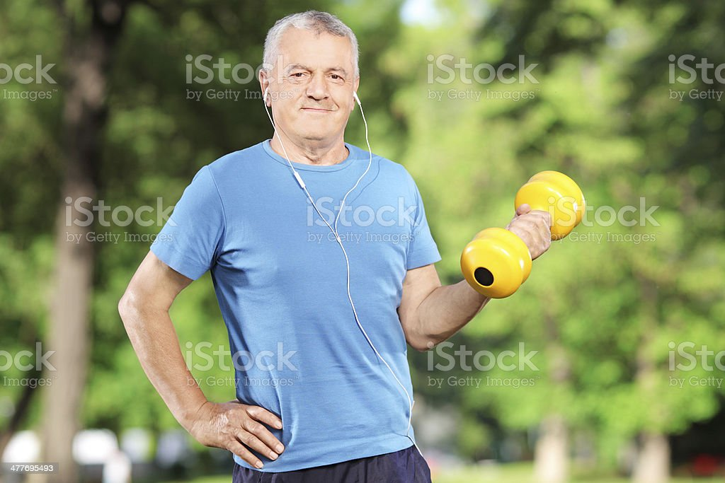 Senior man exercising with weight in park stock photo