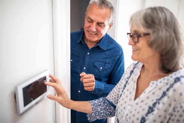 senior mann erklärt seiner frau, wie man einbruchsalarm setzen - alarm stock-fotos und bilder