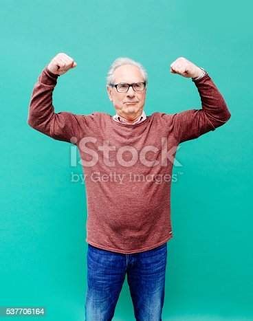 Vintage toned image of a senior man looking happy and strong against a vibrant turquoise background. Positive emotion, strenght, happiness, young at heart concepts.
