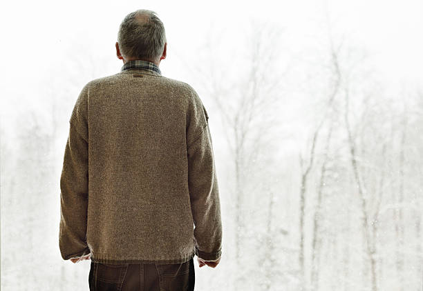 Senior man faces last winter Rear view of a senior man wearing an old sweater in front of cold winter view. His hands are clenched in anxiety as if he were standing in front of his last voyage. one senior man only stock pictures, royalty-free photos & images