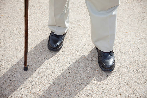 senior man feet and cane walking on sidewalk - old man feet stock photos and pictures