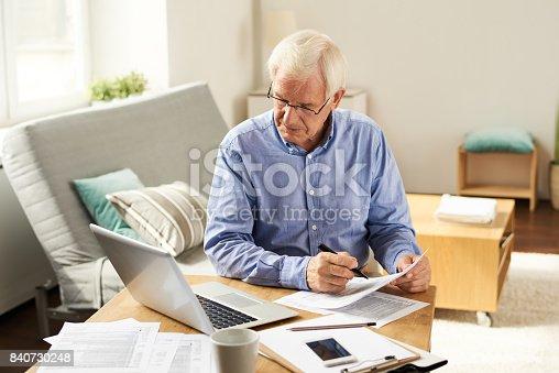 istock Senior Man Filing Tax Report at Home 840730248