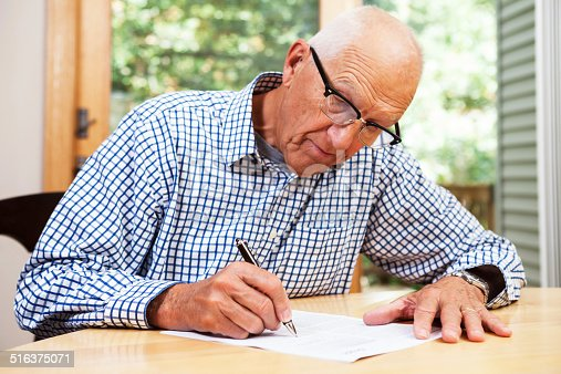 istock Senior Man Filling Out Paperwork, Signing Document 516375071