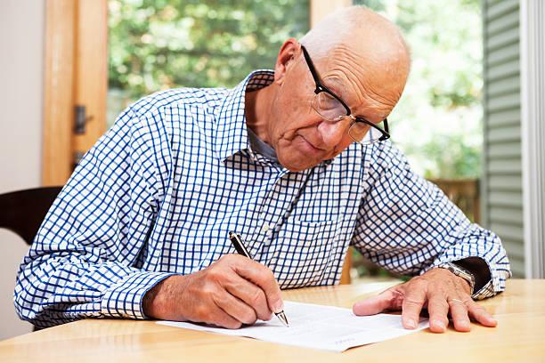 alter mann ausfüllen papierkram, die unterzeichnung des dokuments - formular ausfüllen stock-fotos und bilder