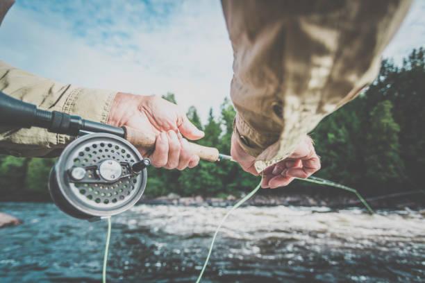 POV Senior Man Fisherman Fly Fishing in A River stock photo