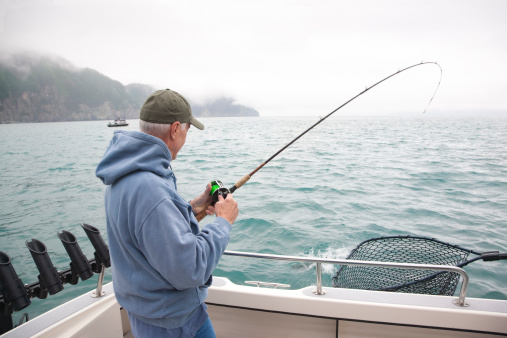 A senior man catches a salmon while fishing in Alaska
