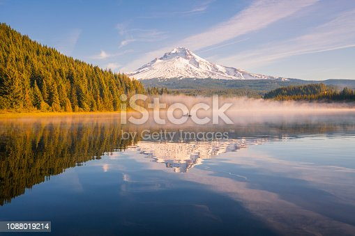 An active senior man fishing on a canoe at Trillium Lake in Oregon at the water's edge of the lake to see Mount Hood peak during sunrise. Fisherman at trillium lake going fishing. Early morning fishing for trout on a canoe or kayak. Golden hour Mount Hood lake Trillium canoe. Mount Hood had golden light shining on the peak at sunrise. A beautiful sunrise at Trillium lake near Portland, Oregon in the Pacific Northwest. Reflections of Mt Hood were seen in Trillium Lake. There were amazing clouds during sunset at Trillium lake with a view of Mount Hood.