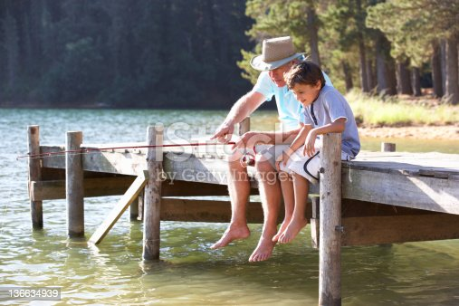483319252 istock photo Senior man fishing with grandson 136634939