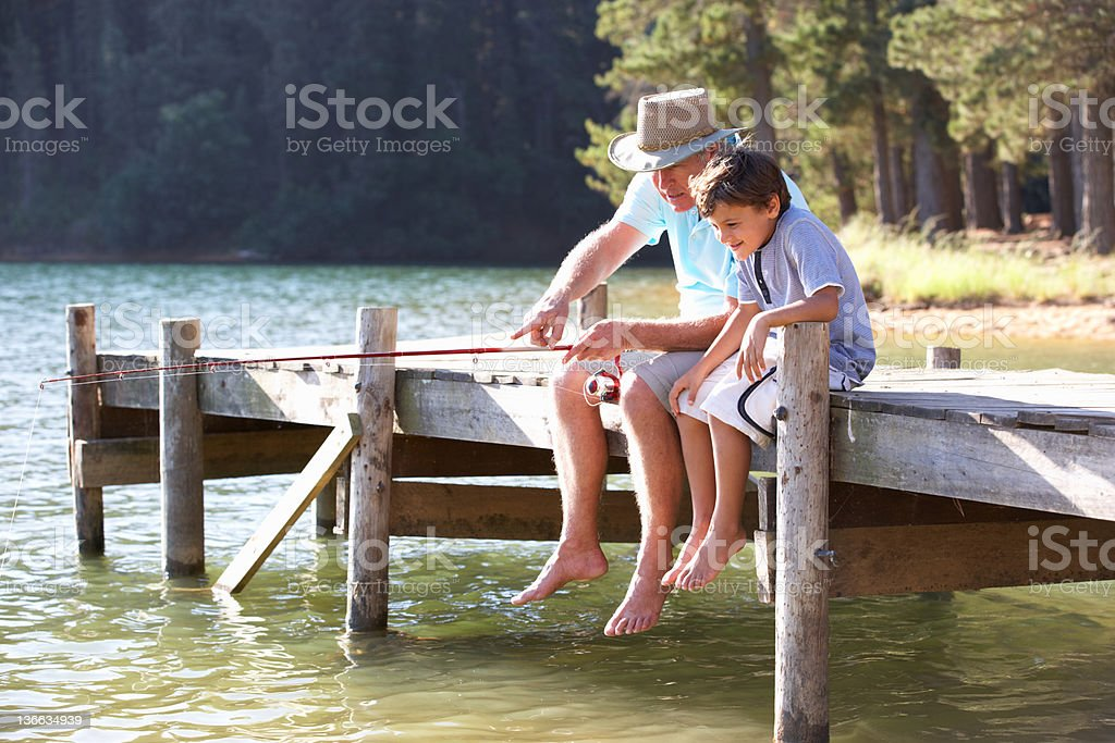 Senior man fishing with grandson stock photo