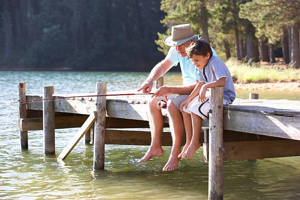 Senior man fishing with grandson stock photo