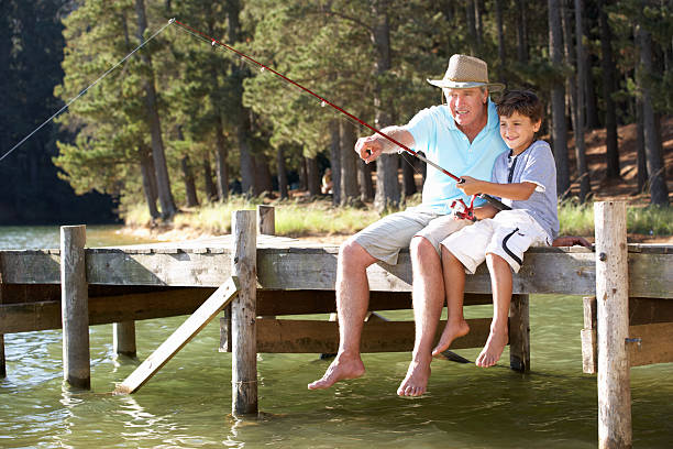 Senior man fishing with grandson Senior man fishing with grandson sitting on jetty freshwater fishing stock pictures, royalty-free photos & images