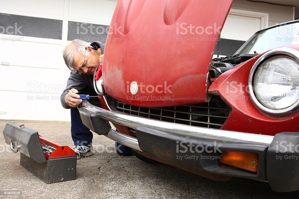 Senior man fixing classic car stock photo