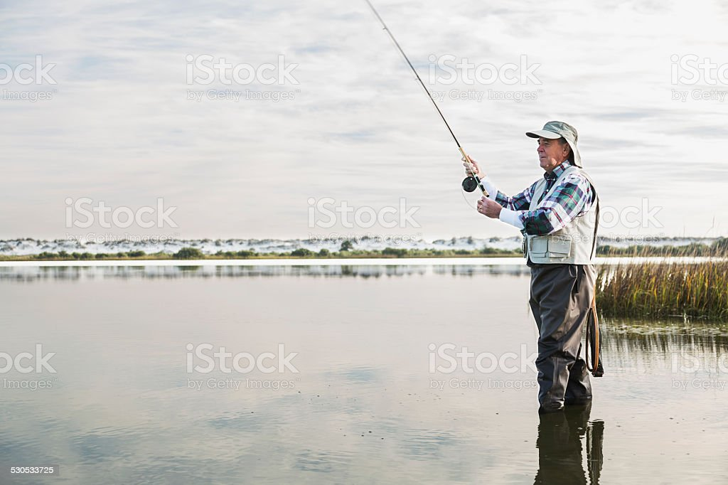 Senior man fly fishing stock photo