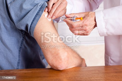 istock Senior man getting an injection from a nurse or doctor 174096972