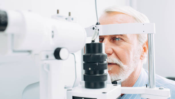 senior man getting eye exam at clinic, close-up - optometrist stock pictures, royalty-free photos & images