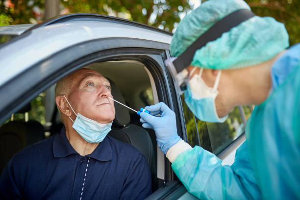 Senior Man Getting Nasal Swab Test at Drive-Thru Site stock photo