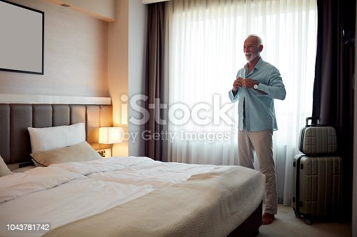 Senior man getting ready for New Year party in his hotel room. Dressing up his shirt and smiling.