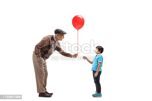 Full length profile shot of a senior man giving a red balloon to a child isolated on white background
