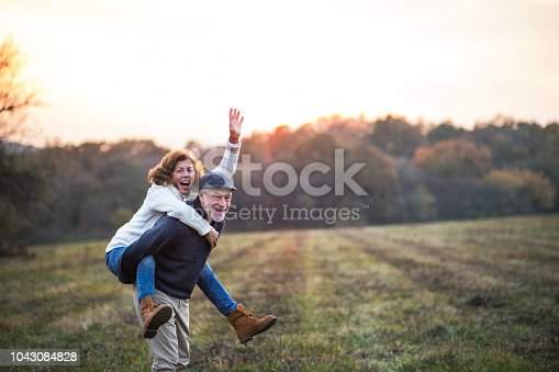 istock Senior man giving a woman a piggyback ride in an autumn nature. 1043084828