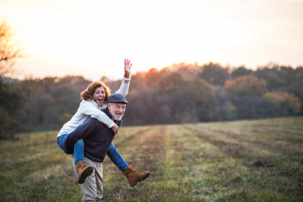 Senior man giving a woman a piggyback ride in an autumn nature. Senior man giving a woman a piggyback ride in an autumn nature. Copy space. piggyback stock pictures, royalty-free photos & images