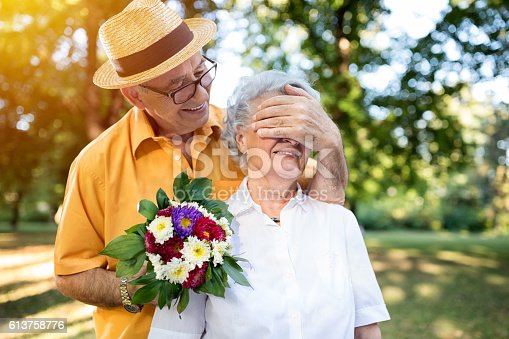 510491454istockphoto Senior man giving bouquet of colored flowers to his wife 613758776