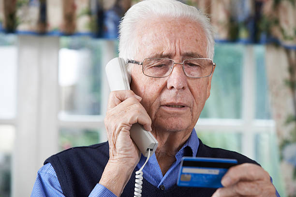 Senior Man Giving Credit Card Details On The Phone Senior Man Giving Credit Card Details On The Phone phone charging stock pictures, royalty-free photos & images