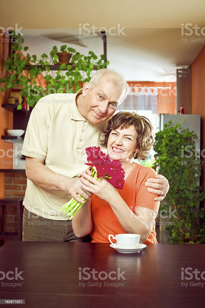Senior man giving flower to his wife royalty-free stock photo